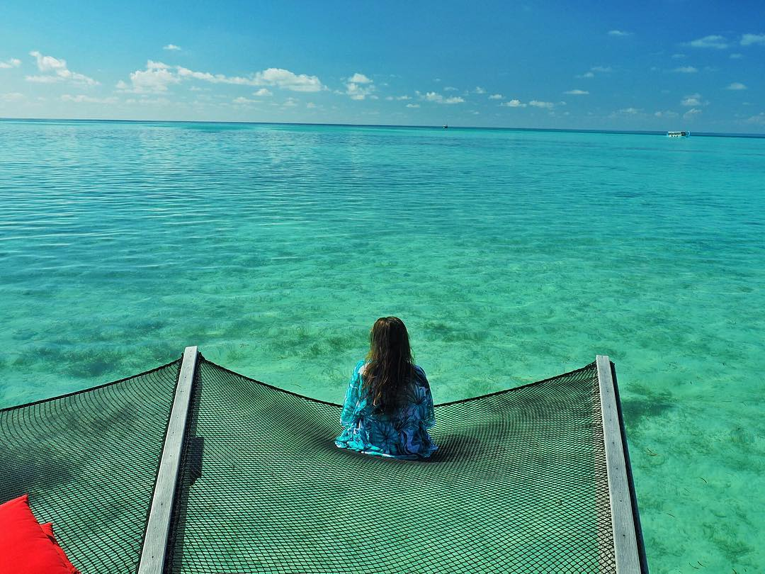 Girl on net over water in Maldives
